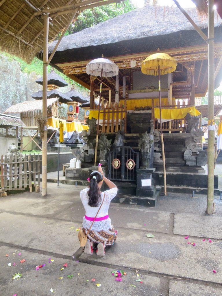 Moça orando diante de um altar hindu em Bali